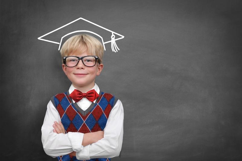 Chłopak na tle tablicy w dorysowanej czapce studenckiej